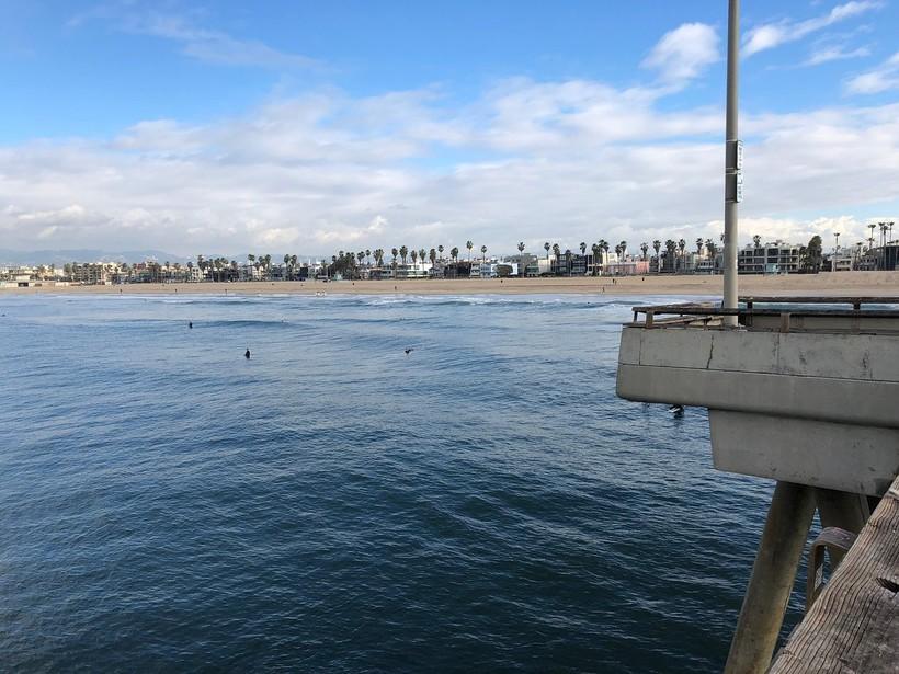 Серферы ловят волну на пляже в Лос-Анджелесе