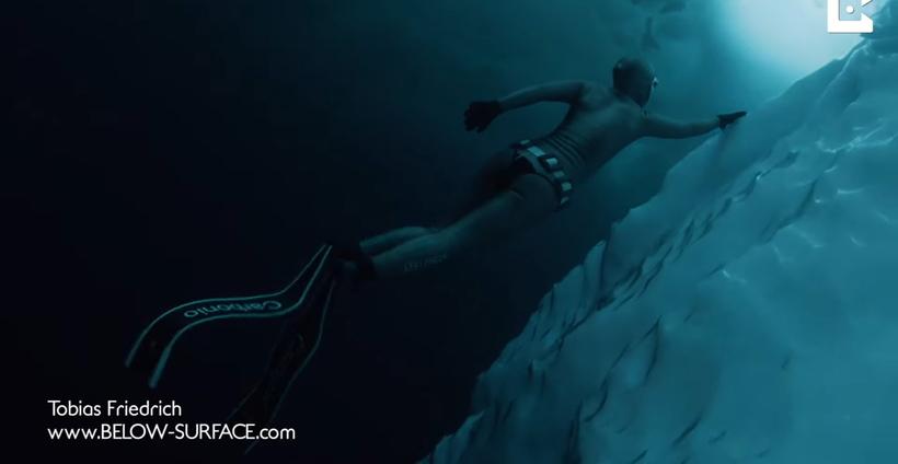Видео: Дайвер проплывает под гренландскими айсбергами